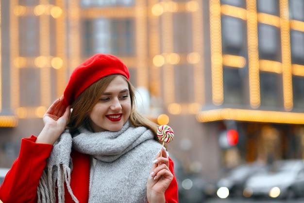 甘いお菓子を保持している赤いコートの美しい若い女性。空きスペース