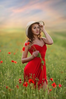Beautiful young woman in red dress and white hat walks around field with poppies