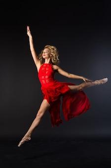 Красивая молодая женщина в красном платье прыгает в балетной позе на черном фоне