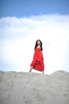 自然の背景に赤いドレスの美しい若い女性