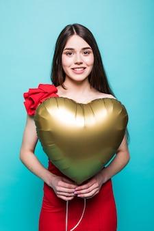ハート形の気球と赤いドレスの美しい若い女性。バレンタインデーの女性。愛の象徴