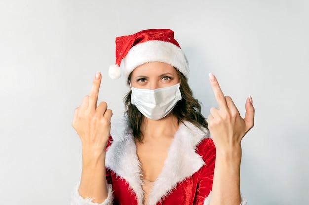 빨간 산타클로스 의상을 입은 아름다운 젊은 여성과 바이러스에 대한 보호 의료 마스크. covid 19 전염병 및 검역에서 크리스마스를 축하하는 개념. 산타 부인은 자가 격리를 싫어합니다