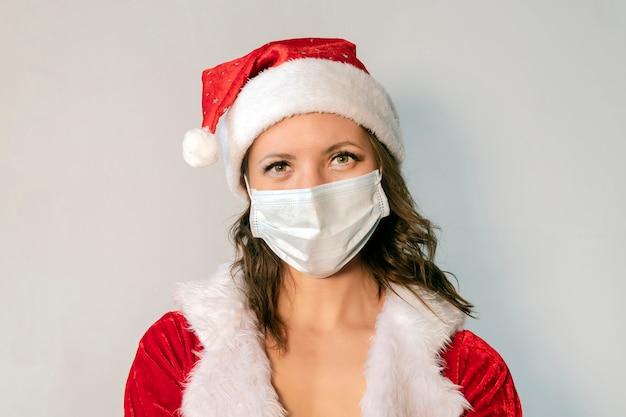 빨간 산타클로스 의상을 입은 아름다운 젊은 여성과 바이러스에 대한 보호 의료 마스크. 코비드 19 전염병 및 검역에서 크리스마스를 축하하는 개념. 메리 크리스마스