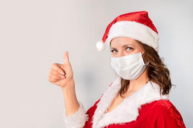 빨간 산타클로스 의상을 입은 아름다운 젊은 여성과 바이러스에 대한 보호 의료 마스크. 코비드 19 전염병 및 검역에서 크리스마스를 축하하는 개념. 엄지손가락을 치켜세우는 산타 부인