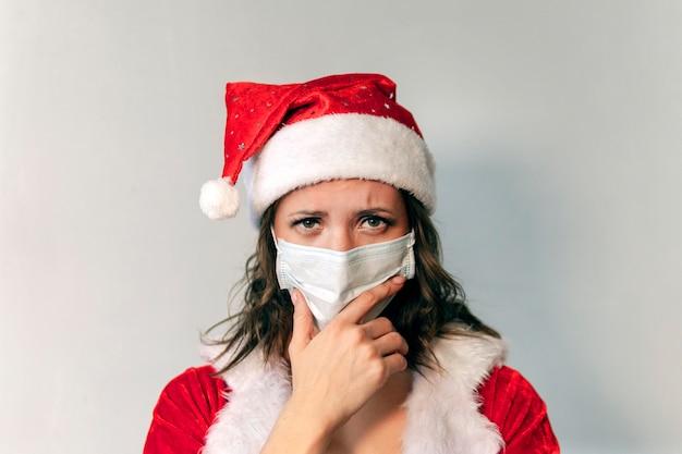 赤いサンタクロースの衣装とウイルスに対する保護医療マスクの美しい若い女性。コビッド19のパンデミックと検疫でクリスマスを祝うというコンセプト。サンタ夫人は悲しくて病気です