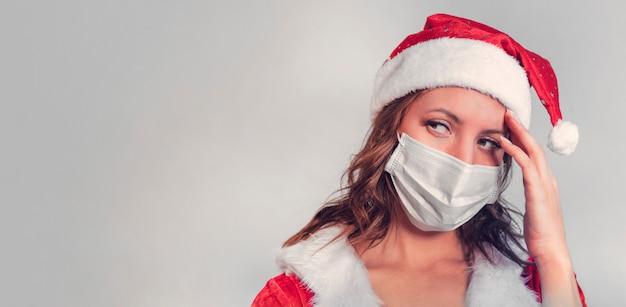 赤いサンタクロースの衣装とウイルスに対する保護医療マスクの美しい若い女性。コビッド19のパンデミックと検疫でクリスマスを祝うというコンセプト。ミセスサンタシックコビッド19。コピースペース