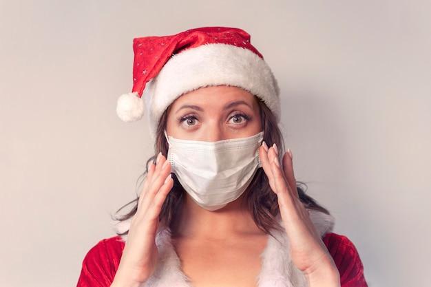 赤いサンタクロースの衣装とウイルスに対する保護医療マスクの美しい若い女性。コビッド19のパンデミックと検疫でクリスマスを祝うというコンセプト。 2020年を恐れたサンタ夫人