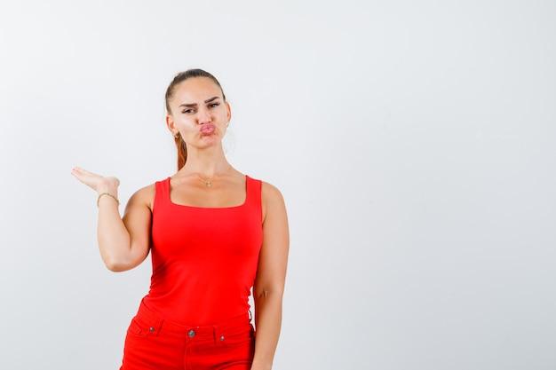 赤いタンクトップの美しい若い女性、何かを保持するふりをして、唇をふくれっ面と自信を持って見えるパンツ、正面図。