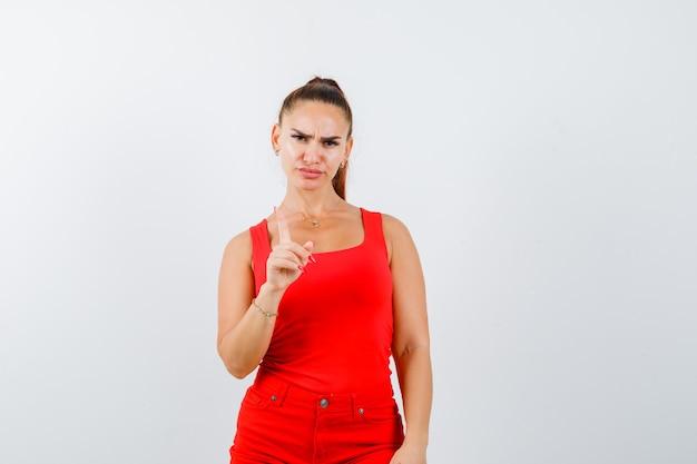 赤いタンクトップの美しい若い女性は、微細なジェスチャーを保持し、真剣に見える、正面図を示しています。