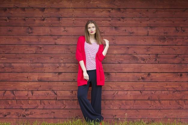 夏に木製の壁でポーズ栗の緩やかな髪と赤で美しい若い女性。