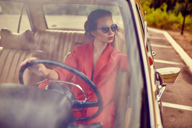 레트로 자동차에서 아름 다운 젊은 여자