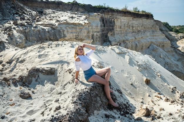 砂の採石場、夏時間の美しい若い女性