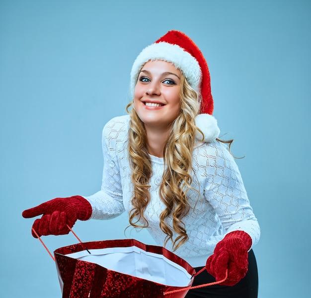 青い背景の上の贈り物とサンタクロースの服を着た美しい若い女性