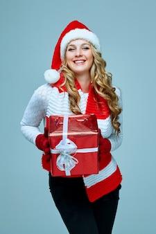 회색 배경에 선물을 들고 산타클로스 옷을 입은 아름다운 젊은 여성