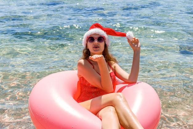 바다에서 풍선 도넛에 편안한 산타 클로스 모자에 아름 다운 젊은 여자