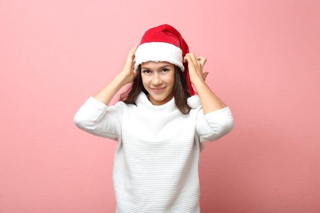 분홍색 표면에 산타 모자에서 아름 다운 젊은 여자