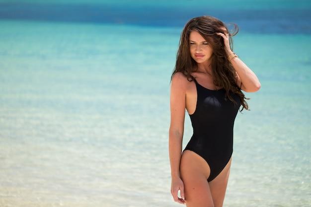 海のビーチでセクシーなビキニ立っている美しい若い女性