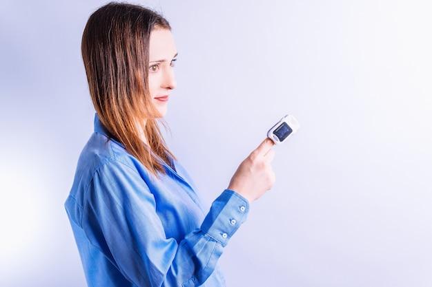 그녀의 손가락에 산소 농도계와 셔츠에 아름 다운 젊은 여자. 제어 및 의료 테스트 개념