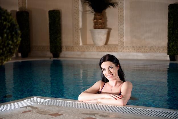 スパで美しい若い女性。女性はプールサイドでリラックスしています。