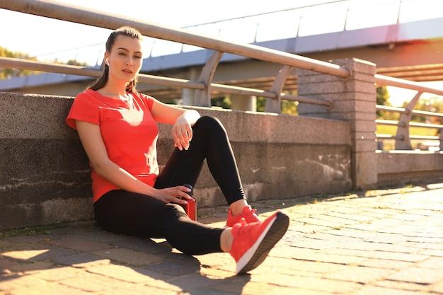 스포츠 의류를 입은 아름다운 젊은 여성이 물을 마시고 저녁 햇빛과 공원 전망을 배경으로 다리에 앉아 있는 동안 피곤해 보입니다.