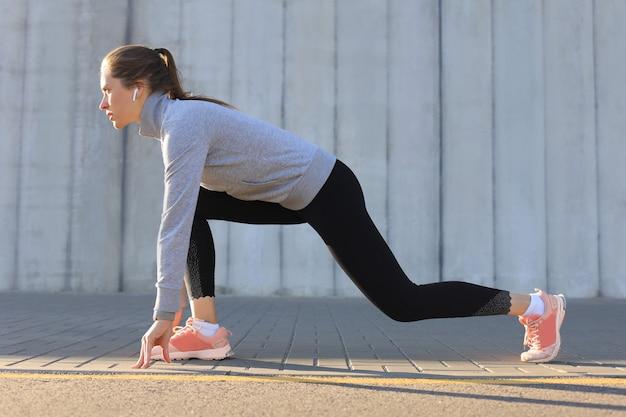 야외에서 달리는 동안 출발선에 서 있는 스포츠 의류를 입은 아름다운 젊은 여성.
