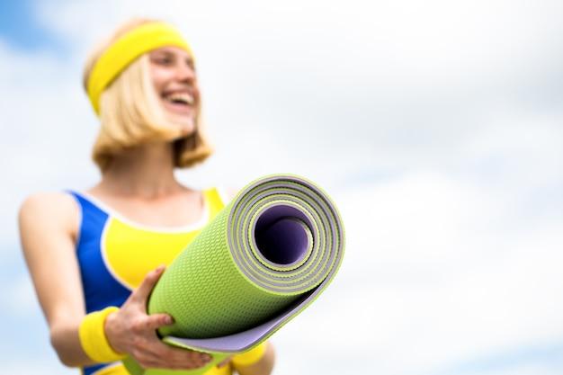 스포츠 착용에 아름 다운 젊은 여자는 요가 매트를 잡고있다.