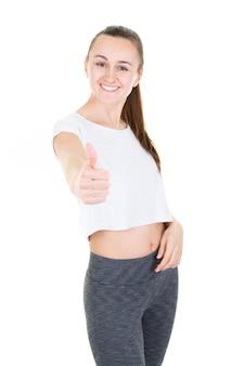 ジェスチャーを親指で示すスポーツウェアの美しい若い女性