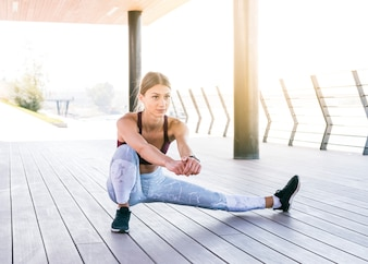 Beautiful young woman in sportswear doing stretching exercise