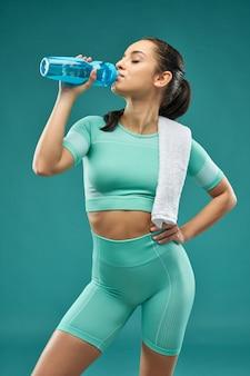 운동복 식수를 입은 아름다운 젊은 여성