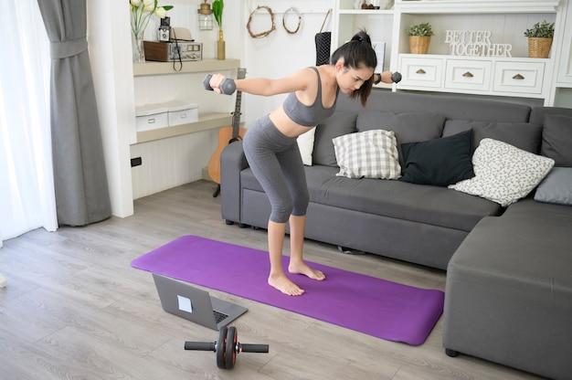 Красивая молодая женщина в спортивной одежде, упражнения с гантелями дома