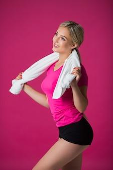 Красивая молодая женщина в спортивной одежде на розовом