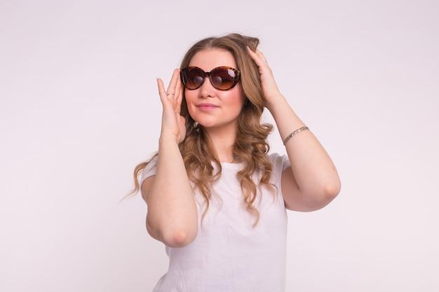 흰 벽에 세련 된 선글라스에 아름 다운 젊은 여자