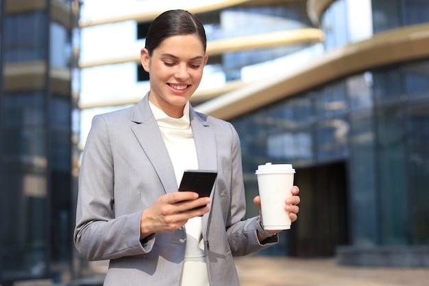 Красивая молодая женщина в костюме с помощью смартфона и улыбается, стоя на открытом воздухе.