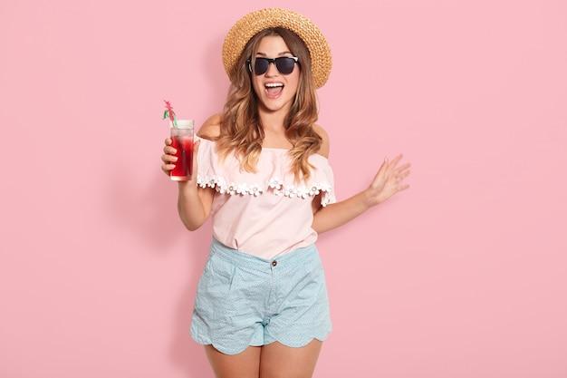 Красивая молодая женщина в летней блузке, короткометражке, шляпе и солнцезащитных очках, держа кувшин с холодным напитком, стоя на розовой стене, любит проводить свое призвание на берегу моря со своими друзьями.