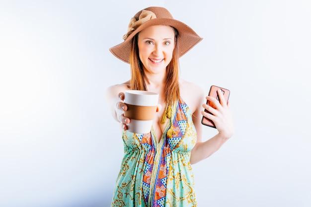 여름 드레스, 모자, 해변 가방을 입은 아름다운 젊은 여성이 커피나 차를 보여주는 스마트폰을 들고 있습니다. 여름 휴가 개념입니다.