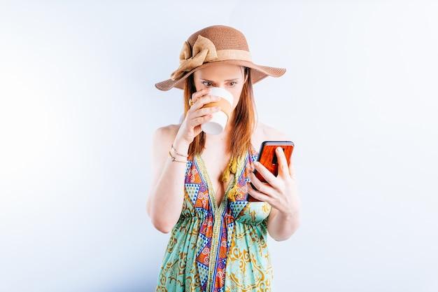 여름 드레스, 모자, 해변 가방을 입은 아름다운 젊은 여성이 커피나 차를 마시는 스마트폰을 보고 있습니다. 여름 휴가 개념입니다. 연결성