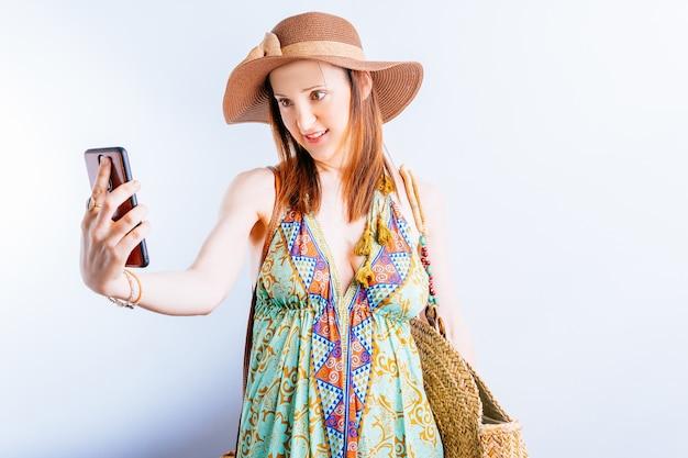 여름 드레스, 모자, 해변 가방을 입은 아름다운 젊은 여성이 셀카를 찍고 있습니다. 여름 휴가 개념