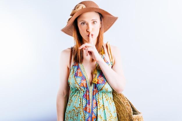 Красивая молодая женщина в летнем платье, шляпе и пляжных сумках, говорящих делая знак тишины. концепция летних каникул. просьба не беспокоить