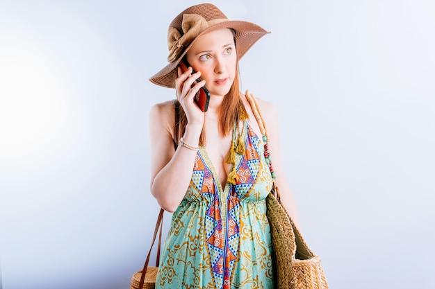 전화 통화 하는 여름 드레스, 모자, 해변 가방에 아름 다운 젊은 여자. 여름 휴가 개념