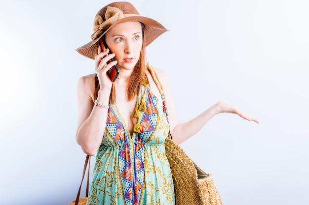 여름 드레스, 모자, 해변 가방을 입은 아름다운 젊은 여성이 여행 문제에 대해 분개하는 몸짓으로 전화 통화를 합니다. 여름 휴가 개념