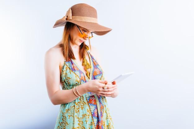 흰색 바탕에 여름 드레스, 모자, 노란색 안경을 쓴 아름다운 젊은 여성이 직장에서 태블릿을 확인하는 복사 공간이 있습니다. 개념 휴가에 일을