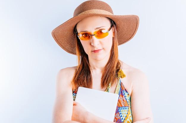 여름 드레스, 모자, 노란색 안경을 쓴 아름다운 젊은 여성이 흰색 바탕에 태블릿을 들고 있는 복사 공간이 있습니다. 휴가 기술 및 연결 개념