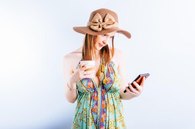 여름 드레스를 입은 아름다운 젊은 여성, 모자는 커피나 차를 마시는 스마트폰을 보고 있습니다. 여름 휴가 개념입니다. 연결성