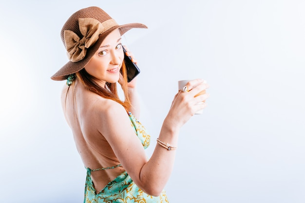 여름 드레스를 입은 아름다운 젊은 여성, 뒤에서 파멜라가 흰색 바탕에 전화 통화를 하는 커피를 들고 돌아섰다. 여름 휴가 개념