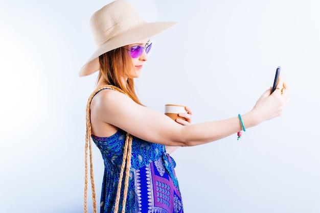 흰색 바탕에 셀카를 찍는 여름 모자 커피와 드레스를 입은 아름다운 젊은 여성