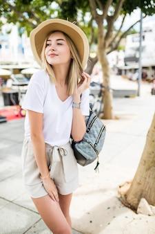 街を歩いている夏の帽子の美しい若い女性。