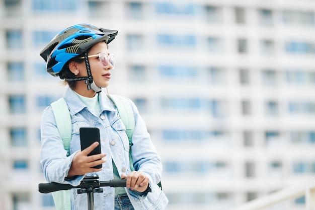電動スクーターの上に立って目をそらしているサングラスと保護ヘルメットの美しい若い女性