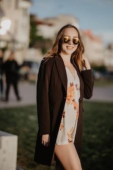Красивая молодая женщина в солнечных очках в городе на закате