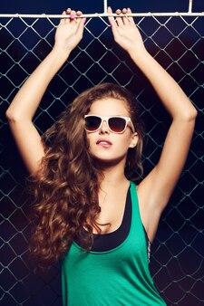울타리 근처 선글라스에 아름 다운 젊은 여자. 아름다운 건강한 머리카락. 색안경. 녹색 티셔츠