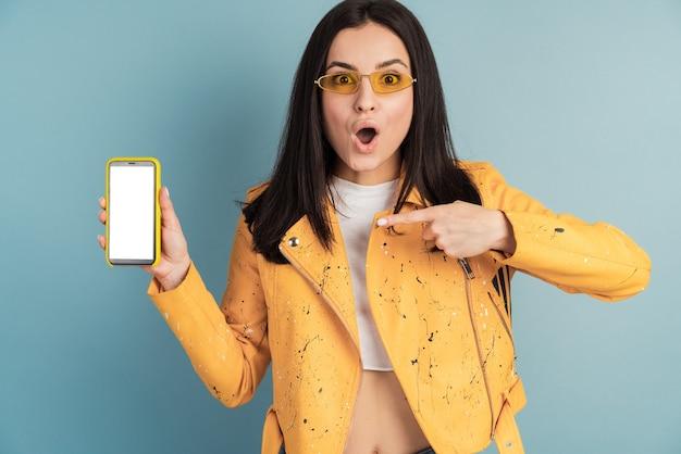 空白の画面の携帯電話を示すサングラスの美しい、若い女性